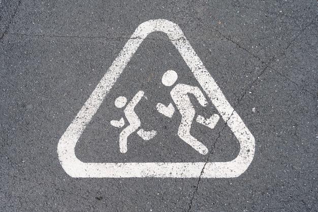 走っている子供、アスファルトに描かれた警告標識