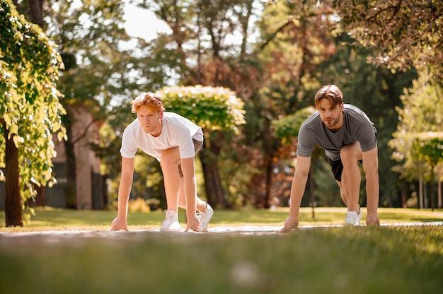 달리기 대회. 화창한 아침에 공원에서 달리기 대회를 준비하는 운동복을 입은 두 명의 성인 남자