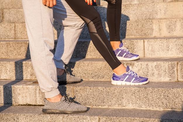 休んでいるカップルを実行しています。リラックスするためのステップで屋外でジョギングトレーニングトレーニング中にボーイフレンドと一緒に立っているランニングシューズと女の子のクローズアップ。