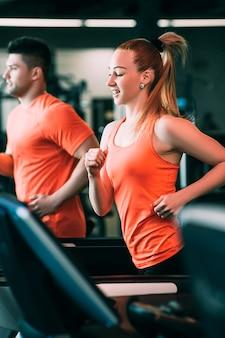 Идущая пара спортивного оздоровительного тренажерного зала. жесткая кардио-тренировка. все для достижения цели.