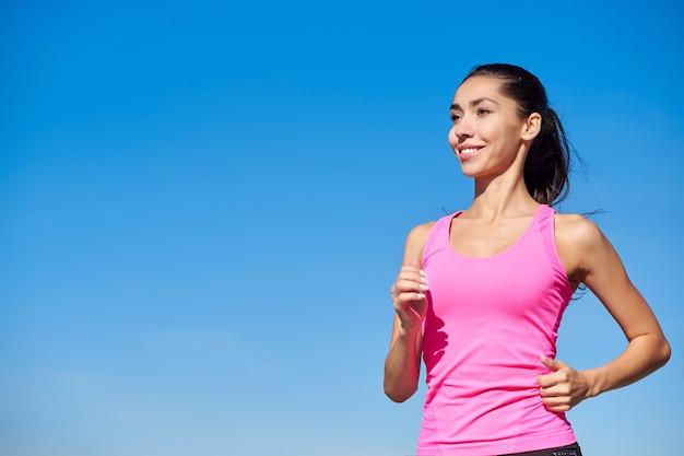 ランニングフィットネスの女性。青い空にピンクのトップでトレーニング女性。
