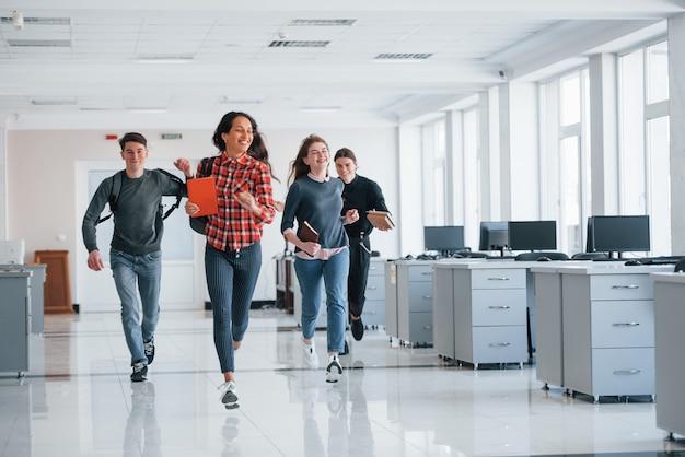Забегая вперед. группа молодых людей, идущих в офисе во время перерыва