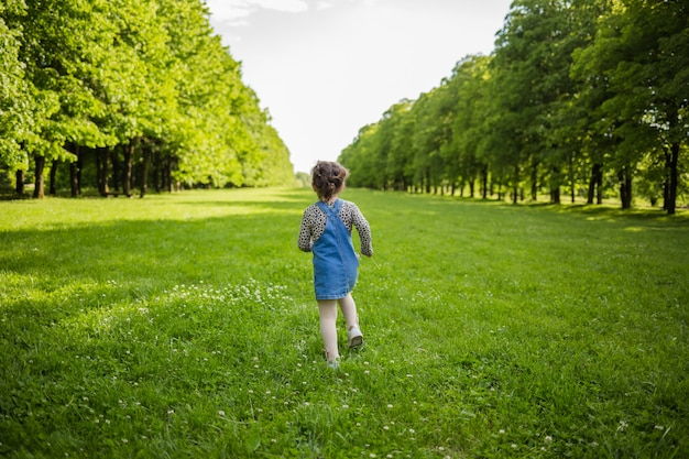 Running girl in a denim sundress in a summer meadow with lime trees.