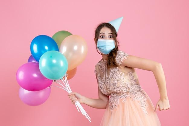ピンクのカラフルな風船を保持しているパーティーキャップと医療マスクとランニングの女の子
