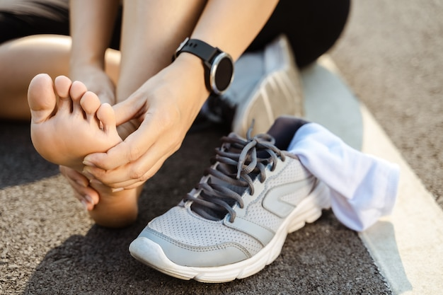 Running injury leg accident. sportive woman runner hurting holding painful sprained ankle in pain. female athlete with joint or muscle soreness and problem feeling ache in her lower body.