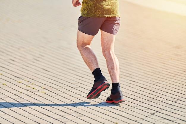 Бегущий мужчина. спортивный (ый) человек, бег в спортивной одежде на городской дороге. здоровый образ жизни, фитнес, спорт, хобби