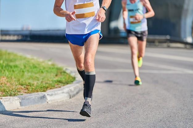 Бегущий мужчина. спортивный (ый) человек, бег в спортивной одежде на городской дороге. уличный марафон, спринт на открытом воздухе. здоровый образ жизни, фитнес-хобби.