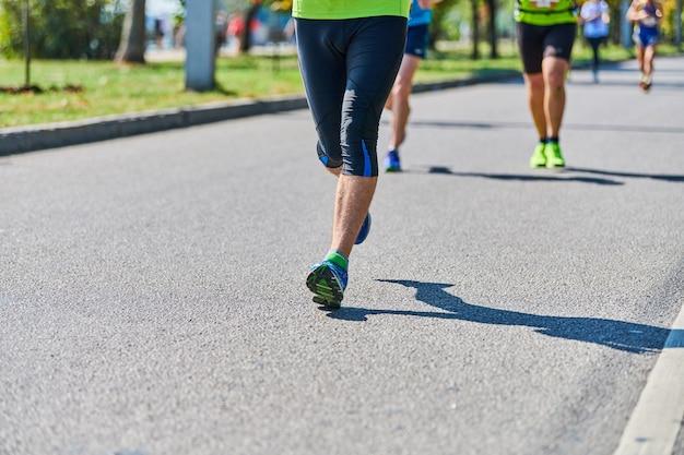 Бегущий человечек. спортивный (ый) человек, бег в спортивной одежде на городской дороге. уличный марафон, спринт на открытом воздухе