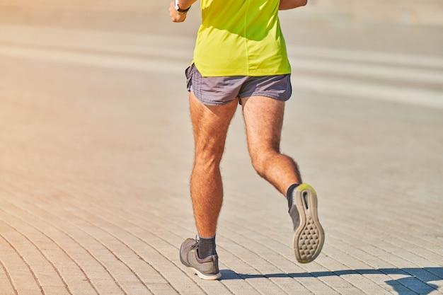 Бегущий человек бегает в спортивной одежде на улице