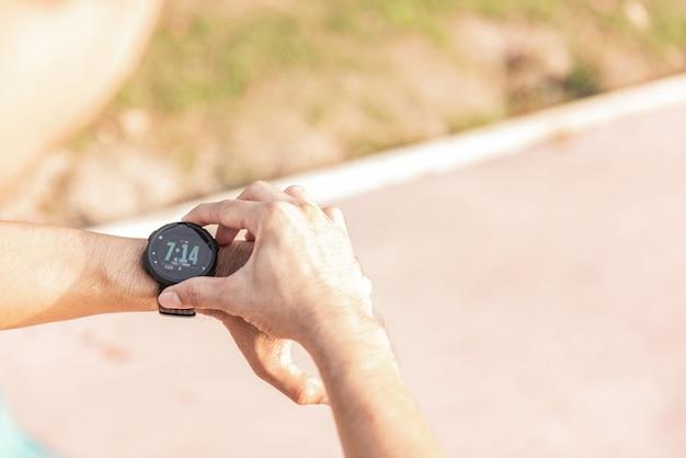 Running man looking sport watch. male jogging using smart watch outside