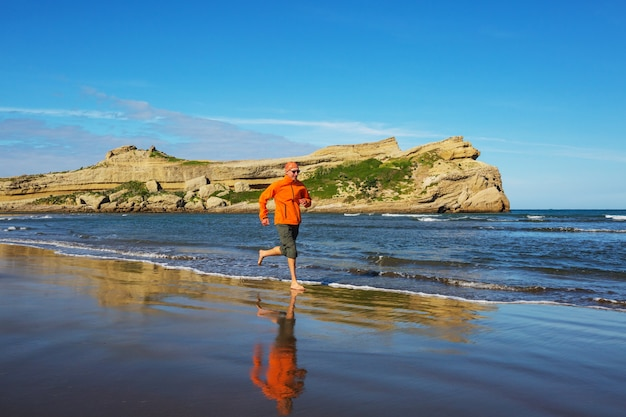 Running man in ocean coast, new zealand