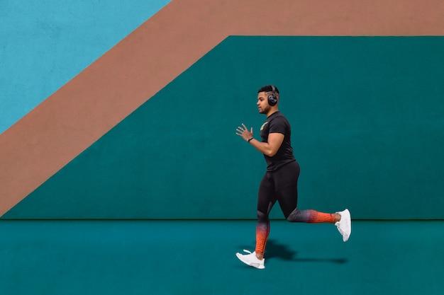 남자 러너 훈련을 실행하고 벽을 따라 야외 도시 달리기 달리기를하는 음악 듣기