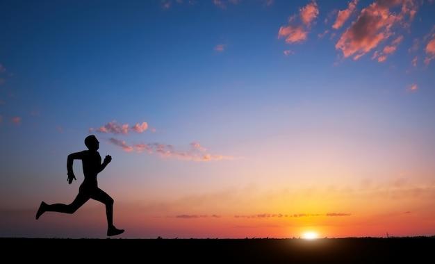日没時に男のシルエットを実行します。スポーツとアクティブライフのコンセプト