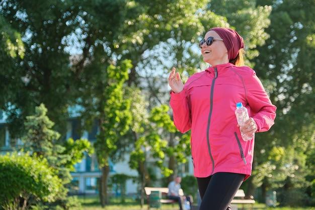 공원에서 물 한 병과 바람막이에 성숙한 여자를 실행. 활동적이고 건강한 생활방식, 아름다움, 중년의 건강, 복사공간