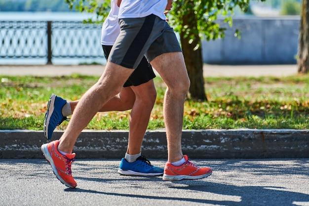 Бегущие мужчины. спортивные мужчины бегают в спортивной одежде на городской дороге