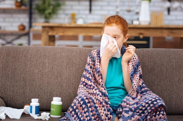 Насморк. милая больная девочка держит бумажную салфетку, страдая от насморка