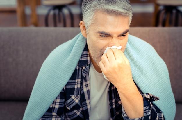 はなたれ。鼻水に苦しんでいる間、紙のティッシュで彼の鼻を拭く不幸な病人