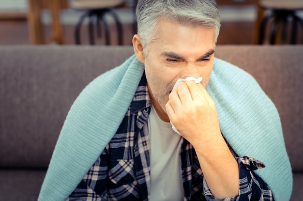Running nose. unhappy sick man wiping his nose with a paper tissue while suffering from the running nose