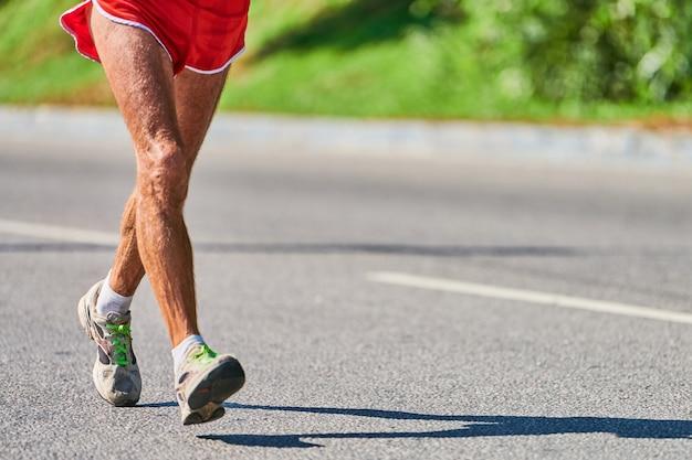 Бегущий старик. старик на пробежке в спортивной одежде по городской дороге. здоровый образ жизни, фитнес, спорт, хобби
