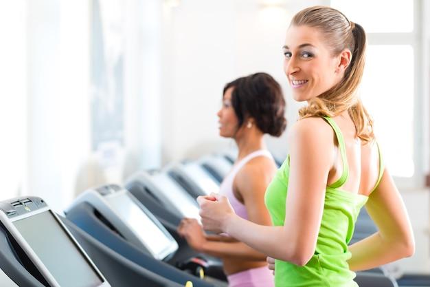 ジムやフィットネスクラブのトレッドミルで走っている-2人の女性がより多くのフィットネスを得るために運動している
