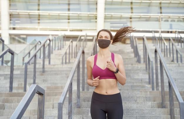 Безопасный бег во время вспышки болезни молодая спортивная женщина в спортивной одежде с защитным лицом