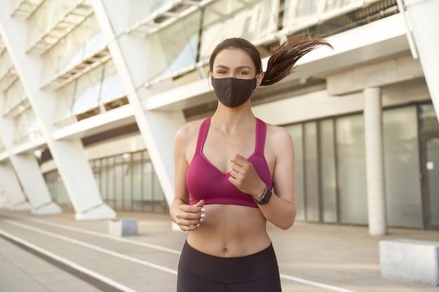 Бегущая безопасно молодая спортивная женщина в спортивной одежде в черной защитной маске работает