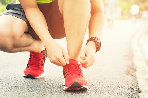 ランニングシューズ男性アスリートが道路でジョギングするために靴ひもを結ぶ