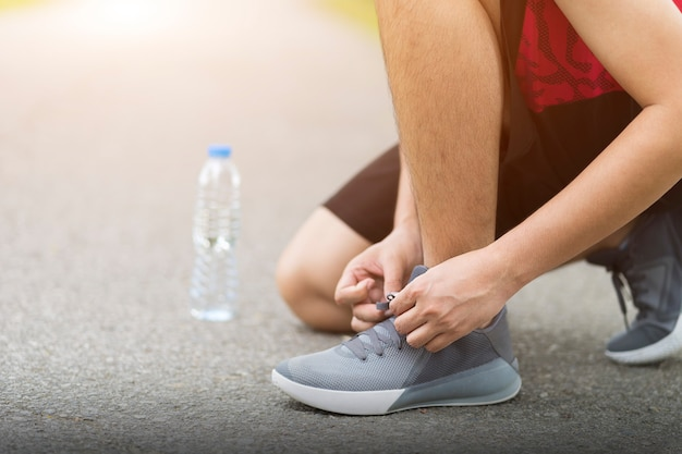 Running shoes - man knee down with tie sneakers shoestring, runner man getting ready for jogging on run way.