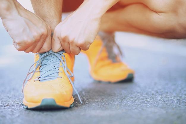 ランニングシューズ-靴ひもを結ぶ男が座っています。ダムロードエクササイズの日の出の時間に屋外でジョギングの準備をしている男性のスポーツフィットネスランナー