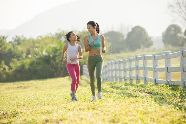 森林公園での秋のランニング シューズ ランナーの女性がひもを結ぶ。ランニング シューズを試すランナーが走る準備をしています。ジョギングの女の子は、健康とフィットネスのモチベーションを高めます。暖かい日差しのフレア。