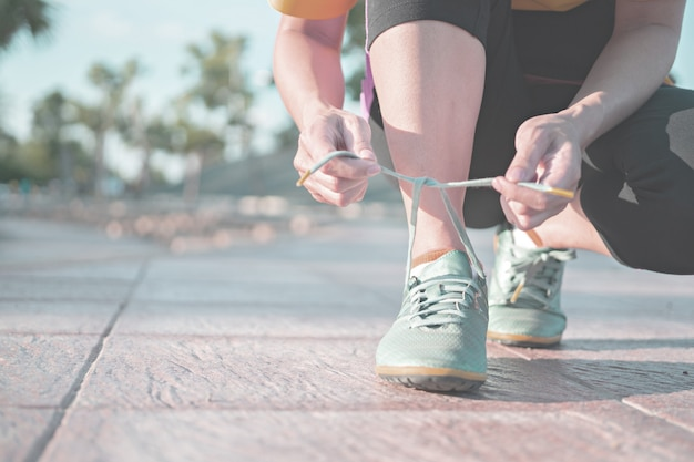 Running shoes - woman tying shoe laces. closeup of female sport fitness runner getting ready for jogging outdoors.