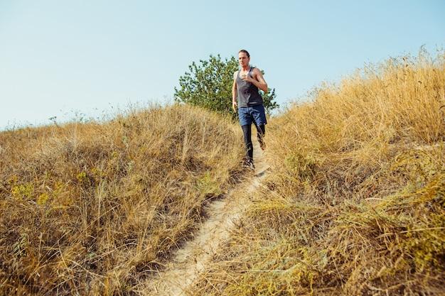 スポーツを実行します。風光明媚な自然の中で屋外全力疾走の男性ランナー。マラソンの実行のために実行している筋肉の男性アスリートトレーニングトレイルに適合します。