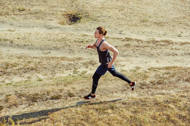 달리기 스포츠. 경치 좋은 자연에서 야외 역주 남자 러너입니다. 마라톤 달리기를 위해 달리는 근육질의 남성 운동 선수 훈련 코스.