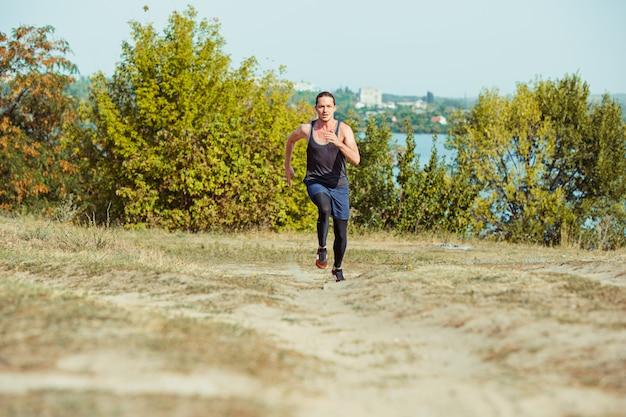 スポーツを実行しています。風光明媚な自然の中で屋外全力疾走の男ランナー。マラソンランニングに適した筋肉質の男性アスリートトレーニングトレイルを装着します。