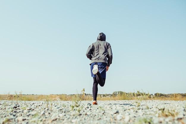 달리기 스포츠. 아름 다운 자연에서 야외 역주 남자 러너입니다. 마라톤 달리기를 위해 달리는 근육질의 남성 운동 선수 훈련 코스.