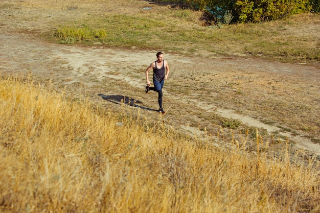 Running sport. man runner sprinting outdoor in scenic nature. fit muscular male athlete training trail running for marathon run.