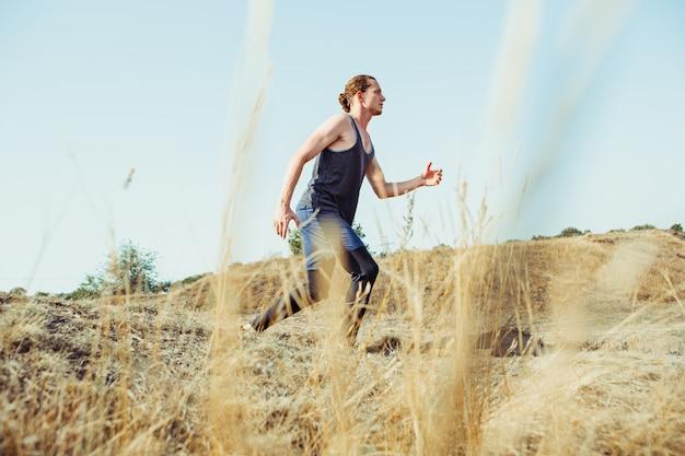Fare sport. sprint corridore uomo all'aperto nella natura scenica. traccia muscolare adatta di addestramento dell'atleta maschio che corre per la corsa di maratona.