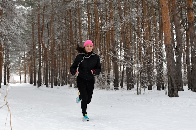 Running sport woman. female runner jogging in cold winter forest wearing warm sporty running clothing and headphones. beautiful fit female fitness model.