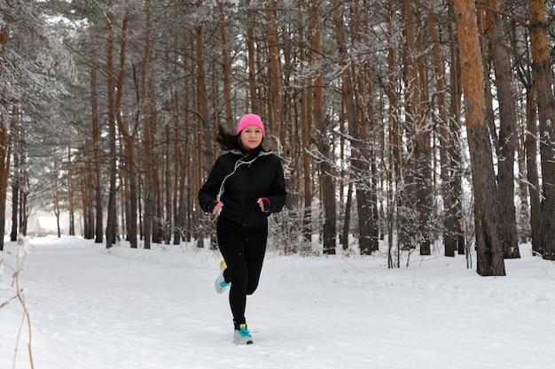 ランニングスポーツの女性。暖かいスポーティなランニングウェアとヘッドフォンを身に着けて、寒い冬の森でジョギングしている女性ランナー。美しいフィットの女性のフィットネスモデル。
