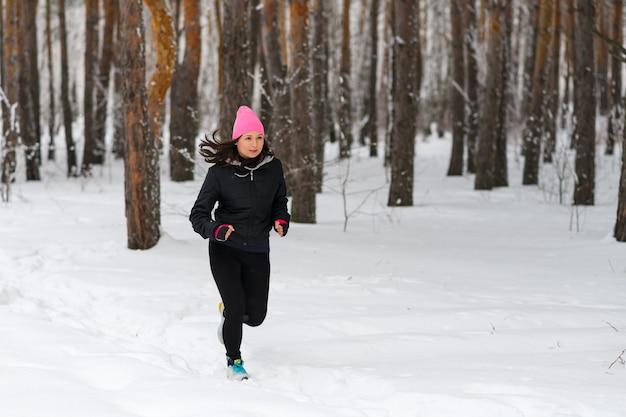 ランニングスポーツの女性。暖かいスポーティなランニングウェアを着て、寒い冬の森でジョギングしている女性ランナー。美しいフィットの女性のフィットネスモデル。