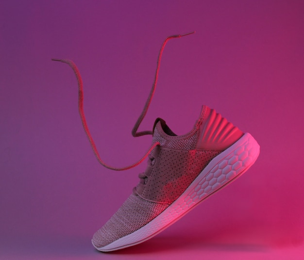 Running sports shoes with flying laces. red neon light