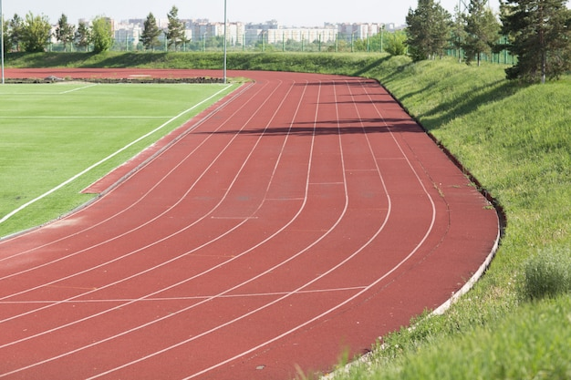 Running track and field with green grass for football at stadium
