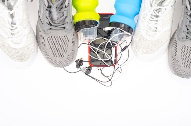 Running track with sneakers and bottle of water on black background. exercise tools for health. studio photo.