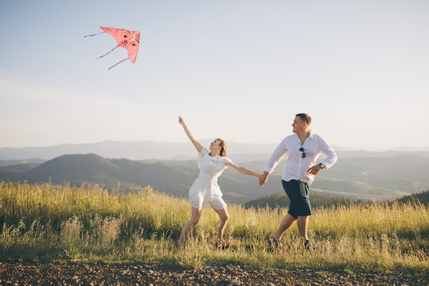 Running with flying kite have fun on countryside. boy and girl running on a hill with a flying kite against a blue sky and sun rays.