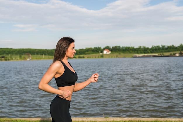 走っている女性。屋外での屋外トレーニング中にジョギングしている女性ランナー。