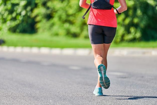 走っている女性。都市道路でスポーツウェアでジョギングするフィットネス女性。健康的なライフスタイル、スポーツの趣味。ストリートワークアウト、屋外での全力疾走