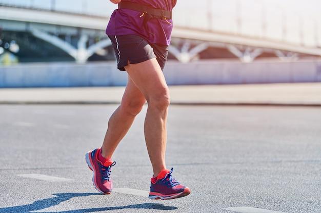 Бегущая женщина. фитнес женщина, бег в спортивной одежде на городской дороге