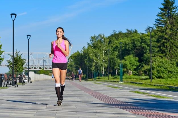 ウォーターフロントで走っている女性。朝のジョギング。アスリートのトレーニング