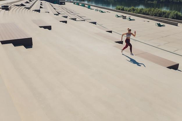 走っている女性。ランナーは日の出でジョギングしています。