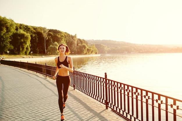 Бегущая женщина. бегун трусцой в солнечный яркий свет. тренировка женской фитнес-модели на улице в парке